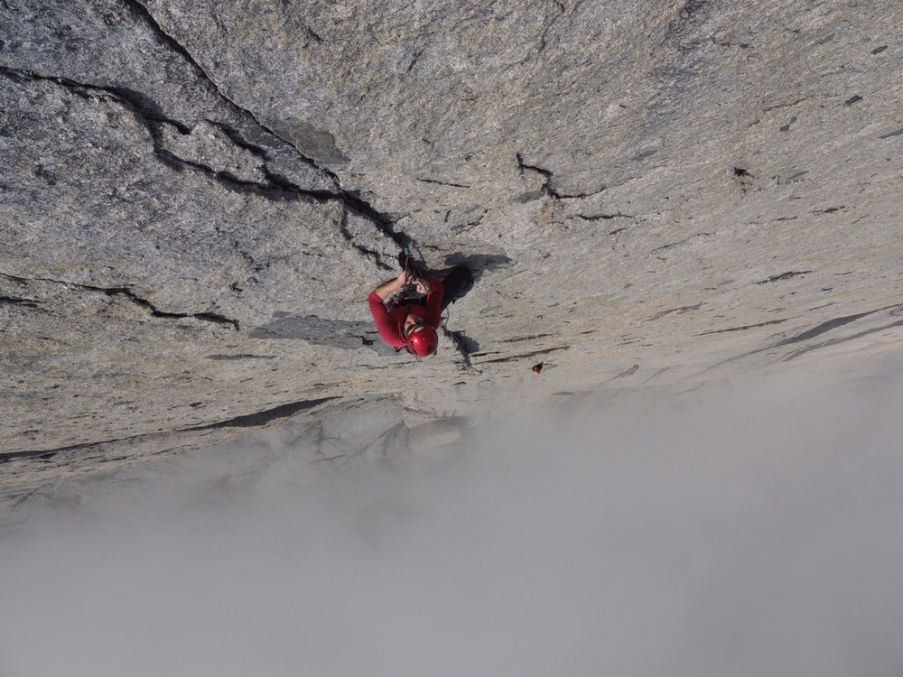 Madeline Sorkin climbs above the clouds on Mount Proboscis. Cirque of the Unclimbables, Northwest Territories, Canada. (Photo by Emily Stifler Wolfe)