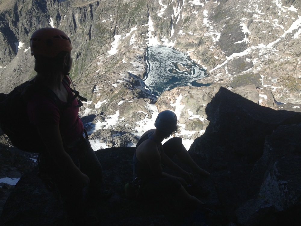 Emily Reinsel and Rose Marks look down from just below the summit of Mount Cowen. Absaroka-Beartooth Wilderness. (Photo by Emily Stifler Wolfe)