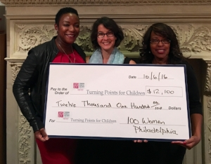 Eartha Holland, Development Director of Turning Points for Children (right) , and Dawn Holden, Turning Points' CFO (left) accept 100 Women Philadelphia's donation from its founder, Elizabeth Zack.
