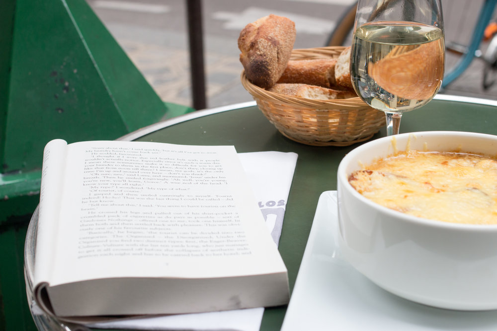 french onion soup and a book in paris, france cafe