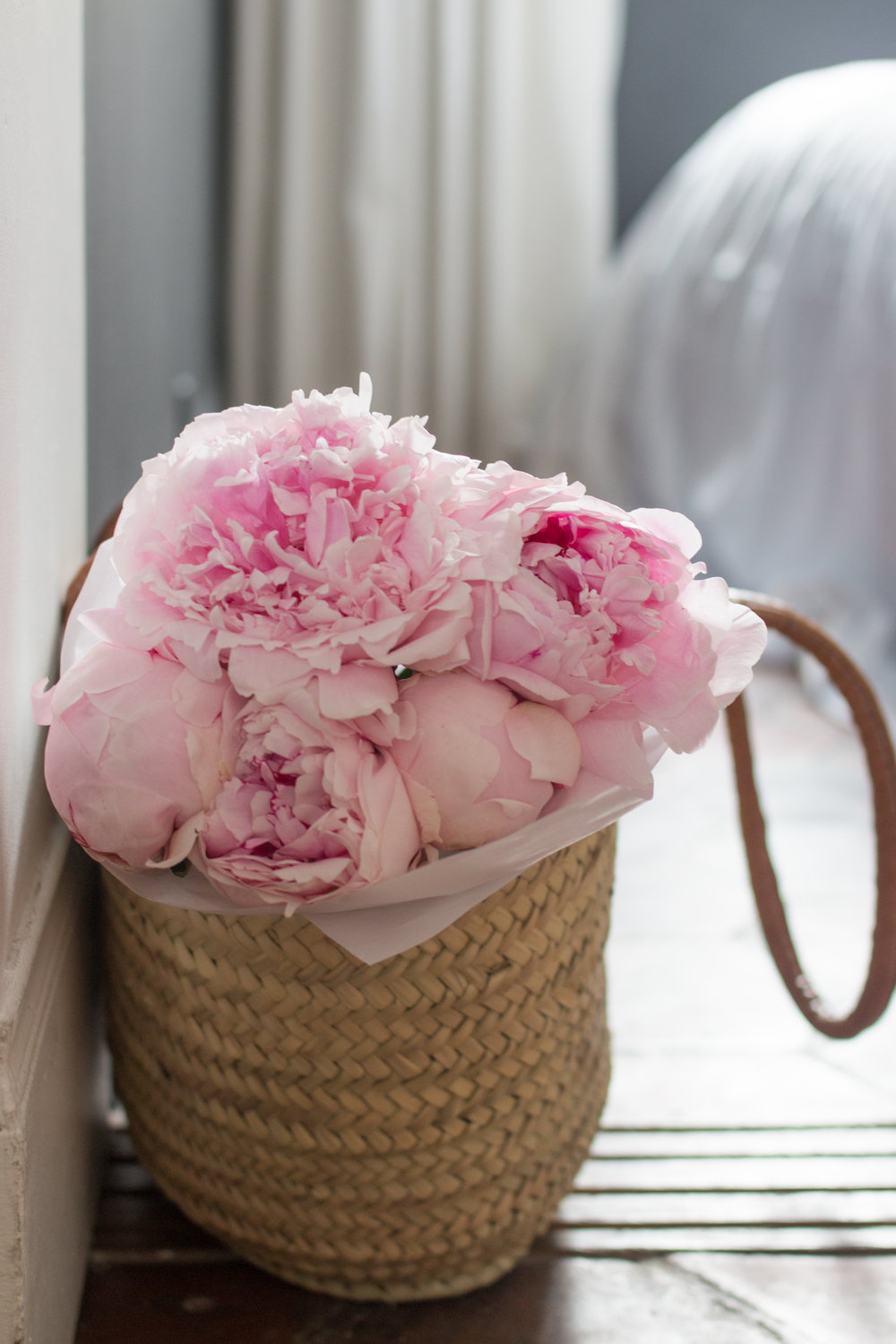 picnic basket with pink peonies in paris, france