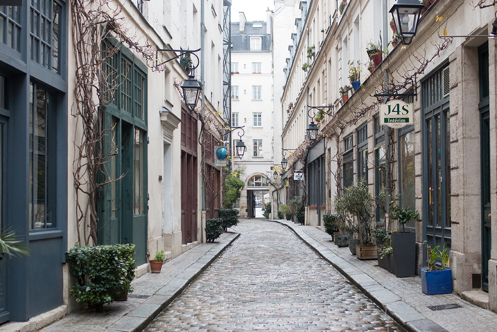rain soaked cobblestone street paris
