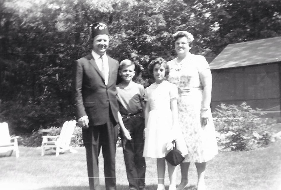 Cynthia with her adopted parents and her brother who was also adopted into the family.