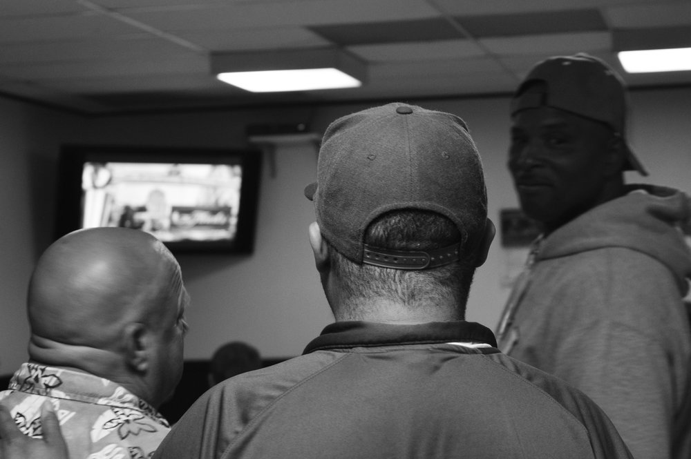 Velton rests his hand on the shoulder of a fellow program attendee while they and the other men watch the Golden State Warriors / Cavaliers game.