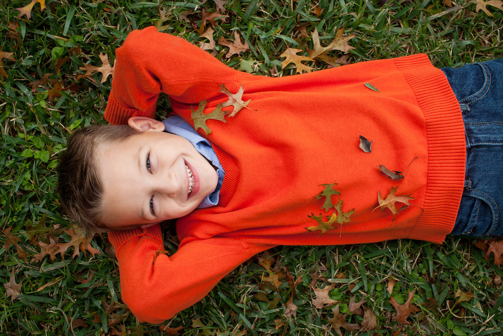 austin boy laying in leaves fall photo shoot