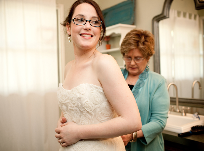 mother of the bride zipping brides dress photograph