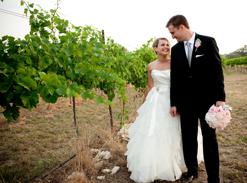 bride and groom holding hands and walking in the vineyard