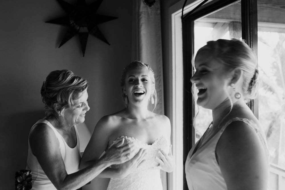 Bride on her wedding day with the mother of the bride and sister of the bride getting ready at destination wedding in puerto rice