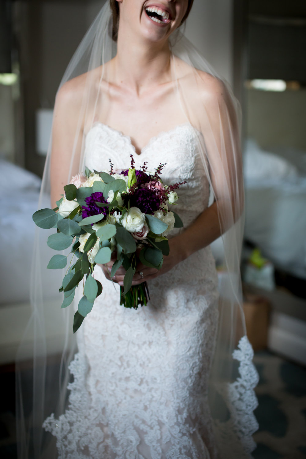 Bride laughing and holding her wedding flower bouquet photographed but the best austin wedding photographer. Bride is wearing a wedidng gown and a cathedral length wedding veil.