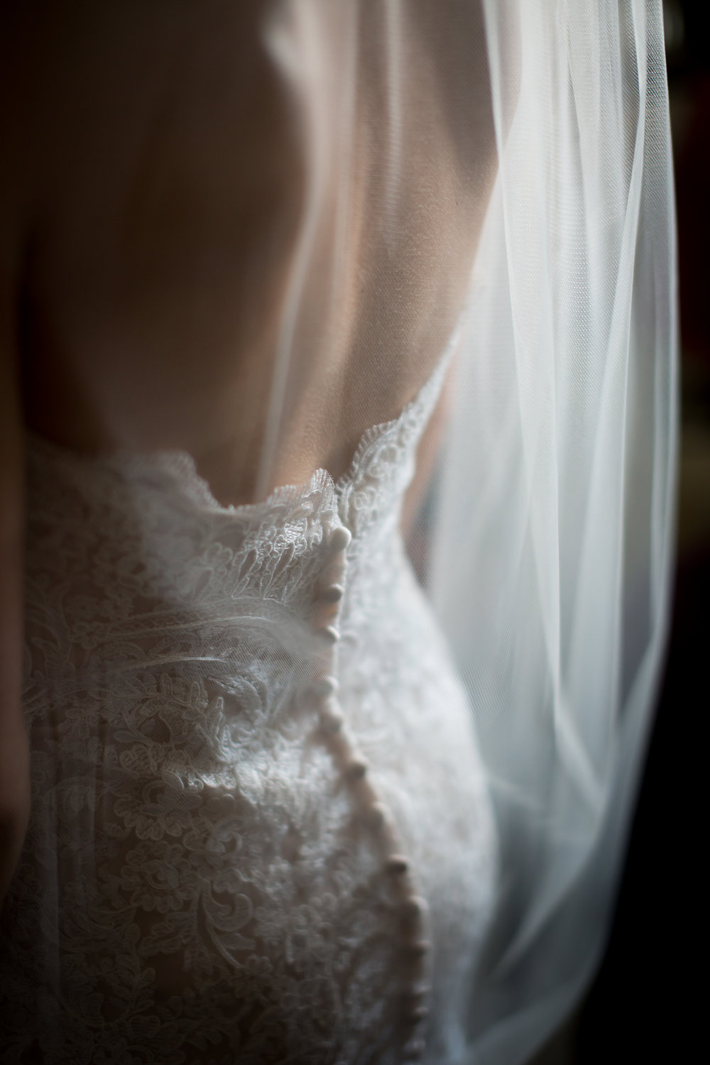 bride in wedding gown detail, buttons down the back of the dress, veil in front moody wedding photograph at Stonehouse Villa in Driftwood Texas