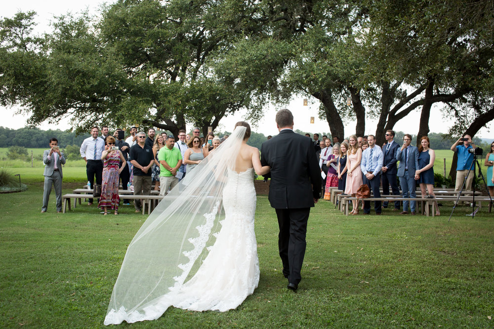 bride and father of the bride walking down the aisle toward the alter during a wedding ceremony at Stonehouse Villa in Driftwood texas, Best Austin Photographer She-N-He