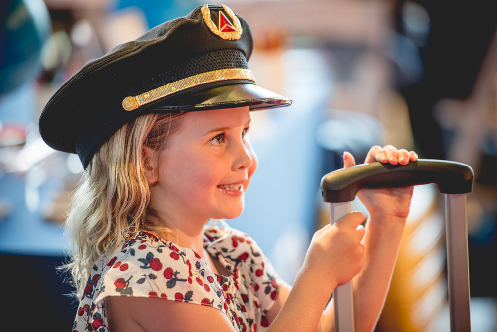 A little lady wearing the pilot's hat and posing for her photo.