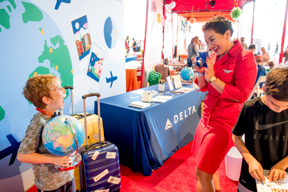 A guest excitedly poses in front of the backdrop while a flight attendant takes his photo!