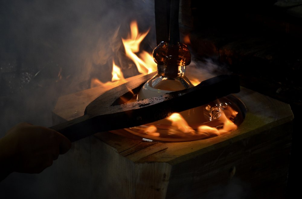 -Blowing glass into wooden mold-