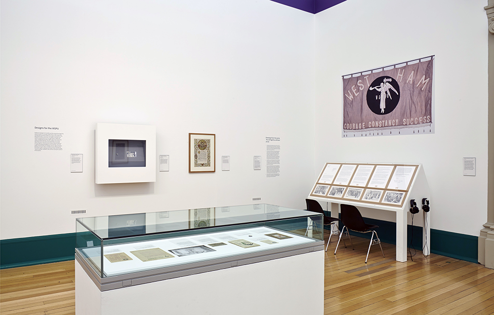 The exhibition included paintings, suffragette campaign materials (including the Holloway Broach - too tiny to see in the far box frame) and archive photographs. The Emily Davison Lodge's artwork, 'The Working Table of the Emily Davison Lodge 2o10-13' can be seen to the left below Sylvia Pankhurst's banner design for the West Ham branch of the WSPU.  Photos: Matthew Booth