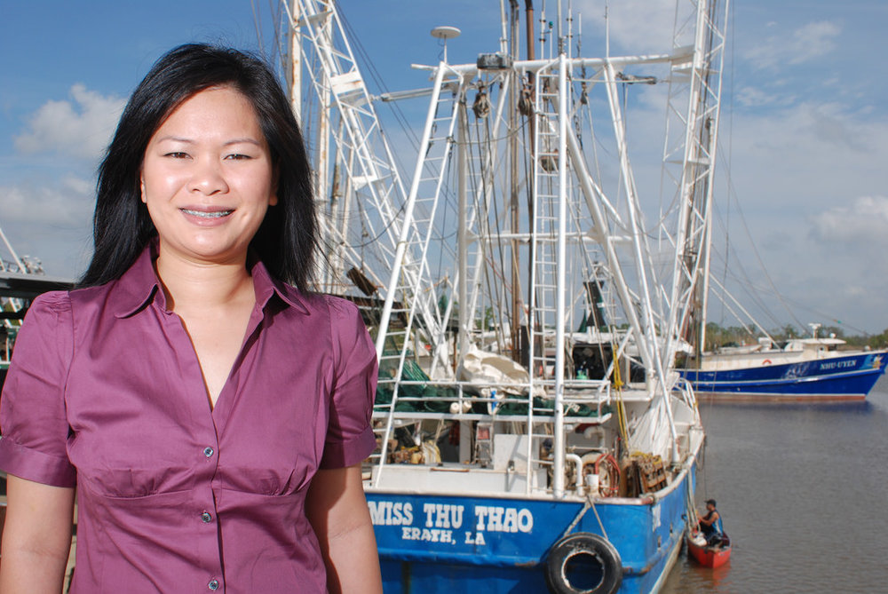 Thu Bui, a fisheries extension agent with the LSU AgCenter, in front of one of her father's shrimp boats. The boats are named after Bui and her sister. Image courtesy of the LSU AgCenter.