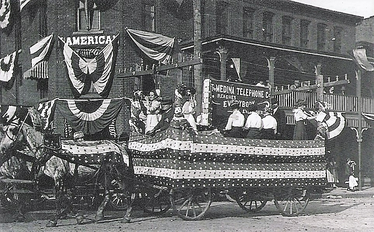 The Medina Telephone Company fancy parade wagon participates in the village 4th of July Independence Day festivities in 1912 as it passes by the decorated American House Hotel owned by Warren J. Anderson on the corner of East Liberty and North Court Streets.