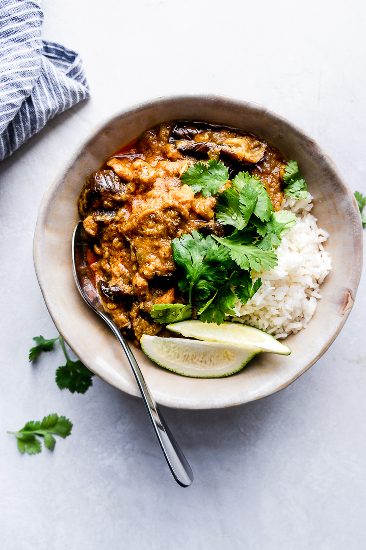 Bowl of coconut chicken curry with eggplant over rice with cilantro and lime wedges