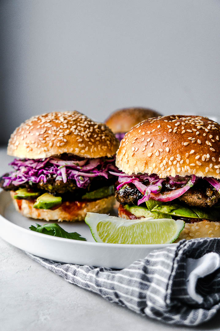 Close-up of two jerk chicken sandwiches on a white plate with a lime wedge