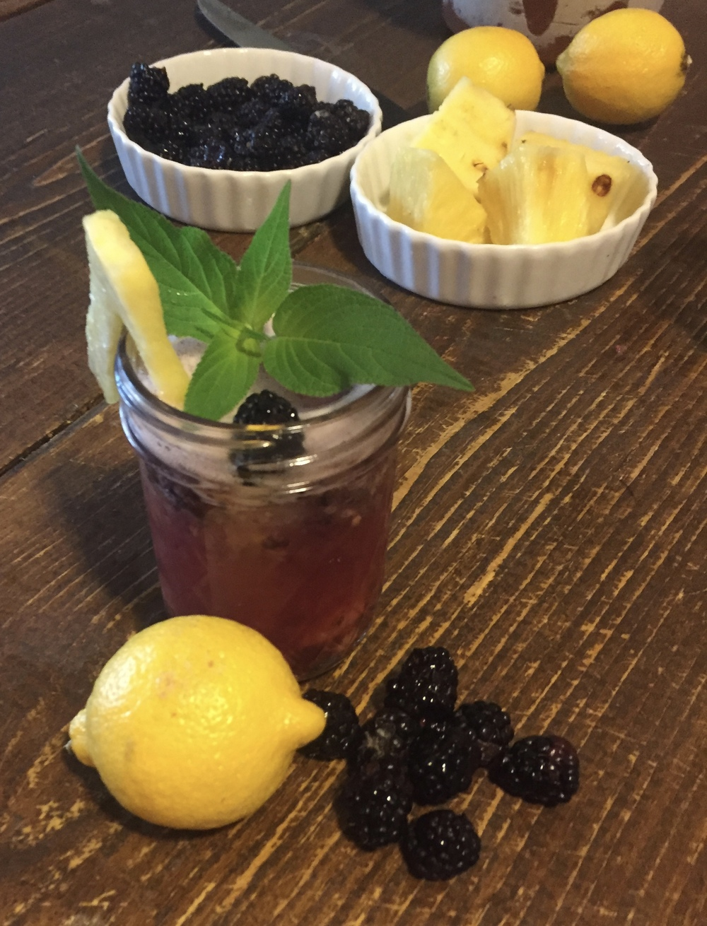 Garnish with a wedge of pineapple, a blackberry, and pineapple sage leaf.