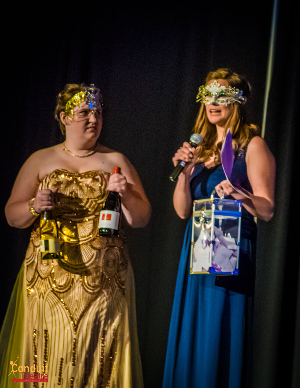Becca Cruger and Aubrey Schulz-Barney of the Greater Grand Forks Young Professionals drawing for prizes at Midnight Masquerade.