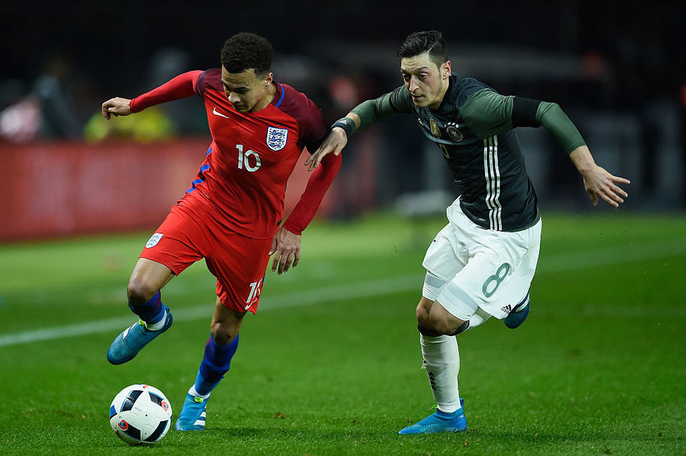 Alli (L) battles with Mesut Özil in a senior international match between England and Germany