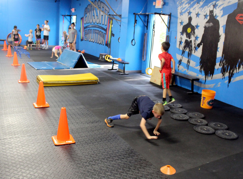 Kids warming up on an obstacle course.