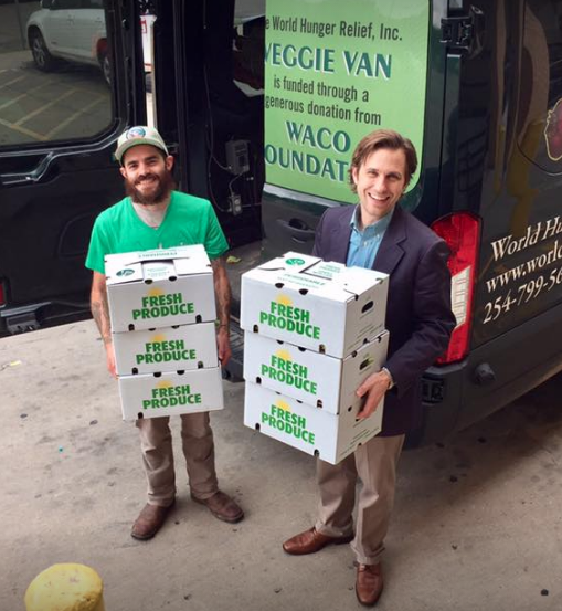 Farm Staff, Daniel Stewart, and Dr. Jackson Griggs of the Family Health Center unload boxes at the main clinic.