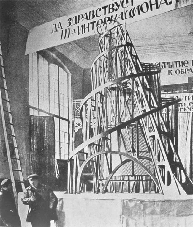 Vladimir Tatlin  (with pipe) before a wooden model of his tower, St. Petersburg, 1920.
