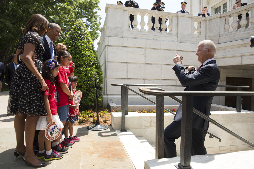 Vice President Joe Biden takes a photo with a cell phone of President Barack Obama, First Lady Michelle Obama, and TAPS Kids on departure from Arlington National Cemetery - 2014.