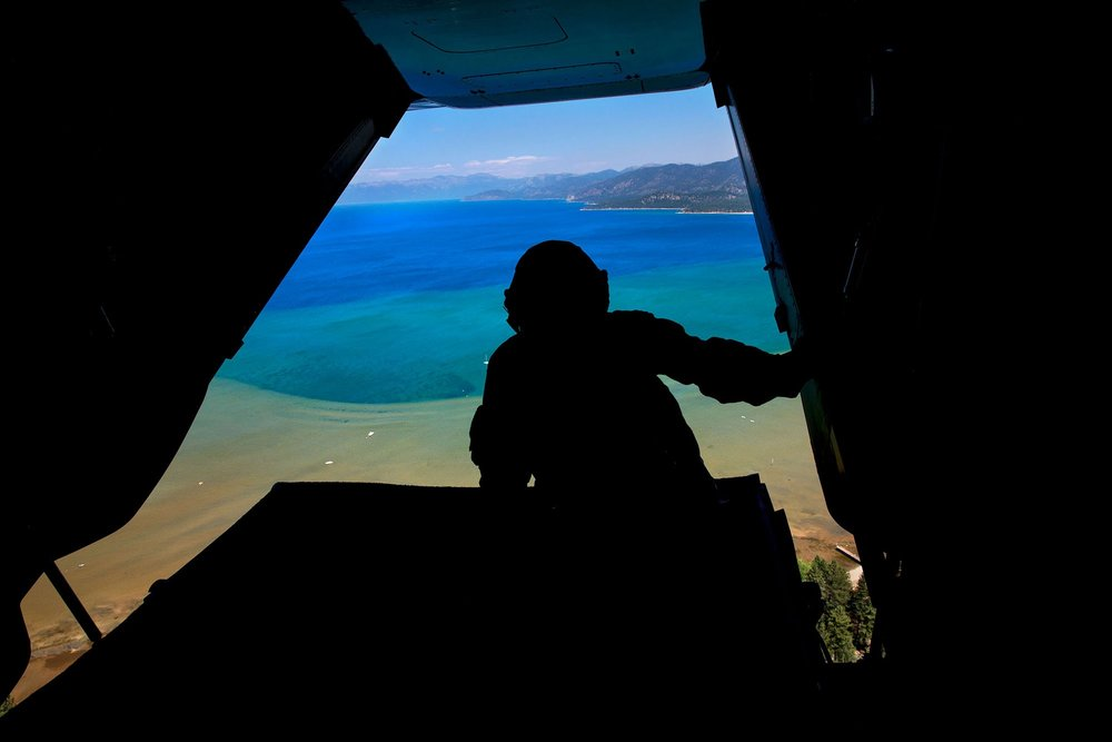 A U.S. Marine Corps crew member looks out the back of Nighthawk-4 en route to the 20th Annual Lake Tahoe Summit in Lake Tahoe, Nev., Aug. 31, 2016.