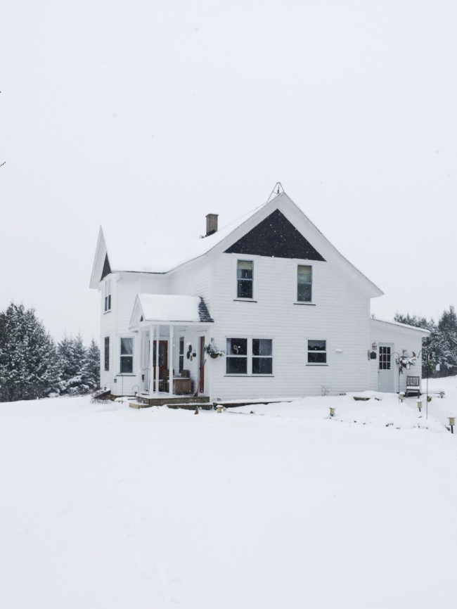 the farmhouse blanketed in fresh snow