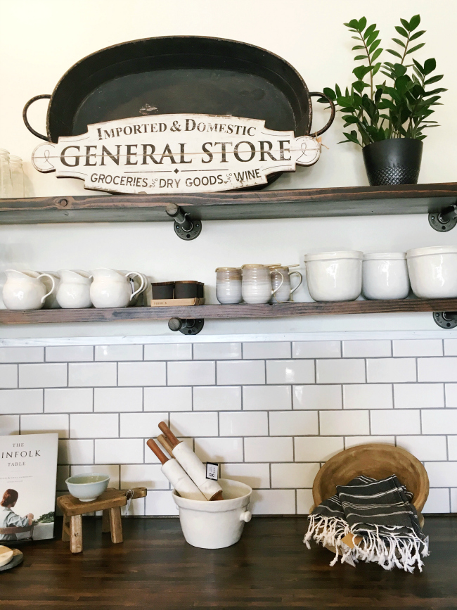 The subway tile & wood shelving houses cute kitchen accents at the Graced home boutique