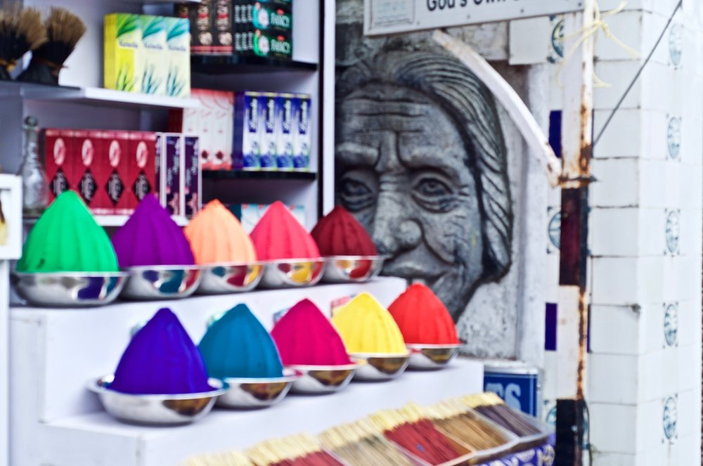 An old woman's face half-hidden by a modern store made pretty for tourists