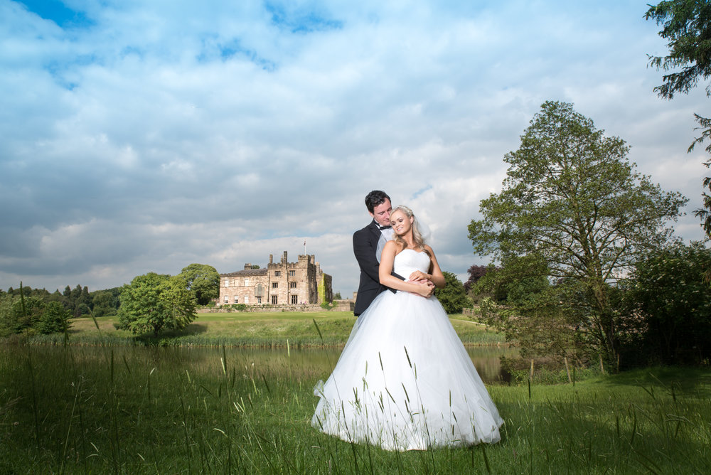 bride and groom beside lake and country house