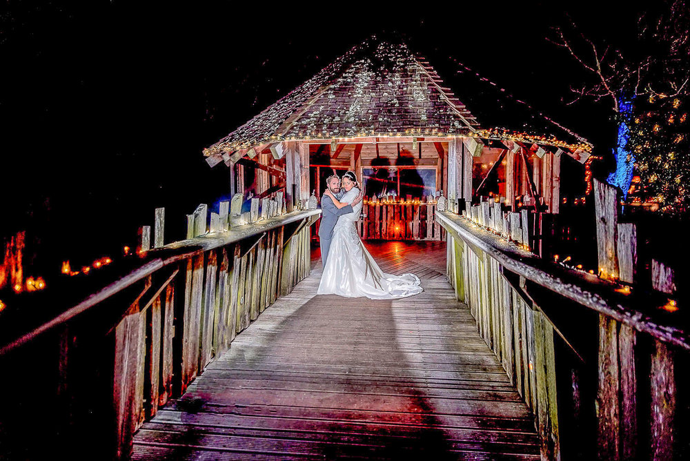 Bride and groom standing at Alnwick Tree House