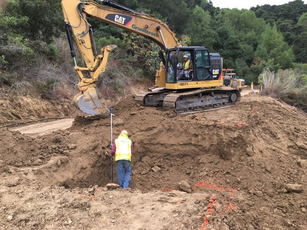 Crews excavating the area as they prepare to install steel pilings at the slope failure site on Redwood Road.