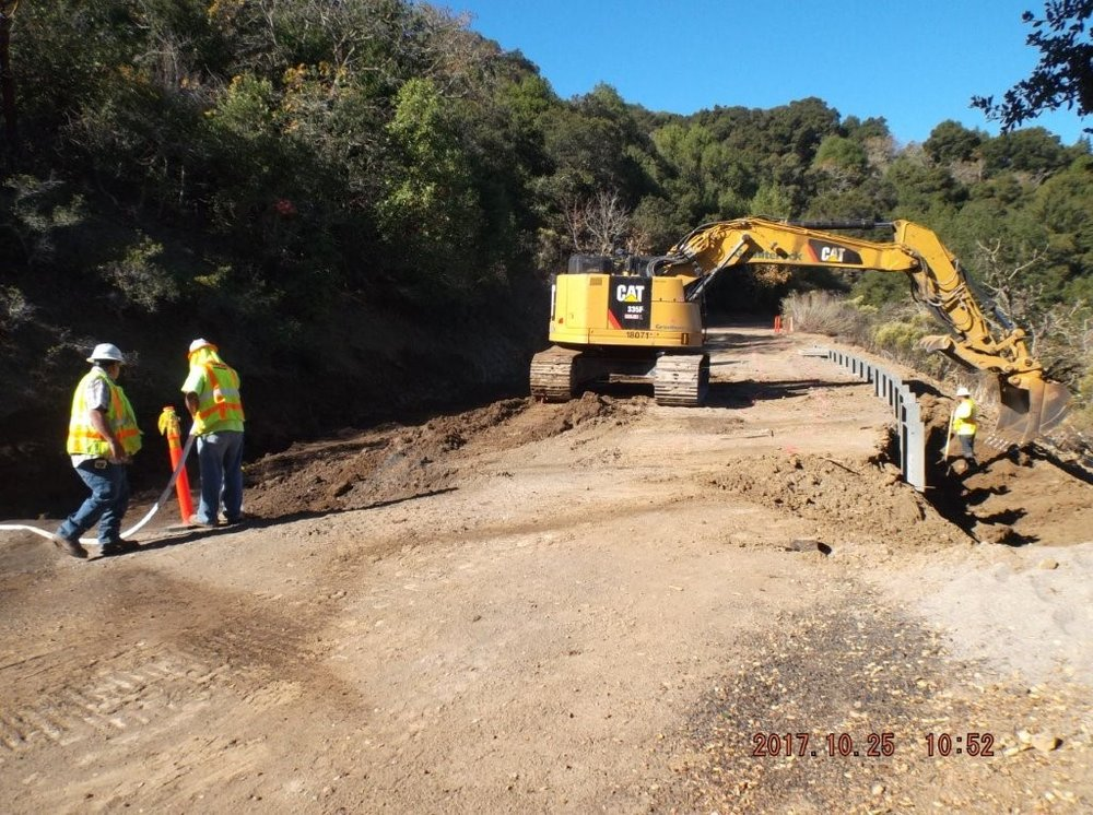 Crews continue the installation of a guardrail and tiebacks on Redwood Road.
