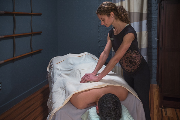 Massage Therapist Amy Montia relieving a patient's lower back pain at Physio Logic.