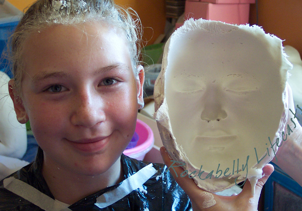 Fran (aged 12) with the mould of her face, just after she's been lifecast. An optical illusion makes the mould look like a complete cast, but it is in fact a negative impression of the face - just like a jelly mould!
