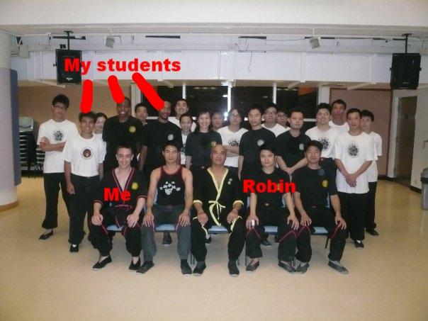 Hong Kong 2009:  In Hong Kong an der Baptist University Wing Tsun Klasse in 2009 with three of my students. Sifu Leung Koon, der Bruder von Sifu Leung Ting, sitzt in der Mitte. Links von Sifu Leung Koon's ist der Tasten-Krieger Robin Tsang, ich sitze ganz links vom Foto. Wie man sieht war ich vor 7 Jahren noch real und kein Betrueger und ein so qualifizierter Wing Tsun Sifu, so dass man mir erlaubte in der ersten Reihe zu sitzen. Robin muss wohl davon ausgehen, dass ich seitdem all mein Wing Tsun vergessen habe und seit dem nicht mehr weiter trainiert habe.