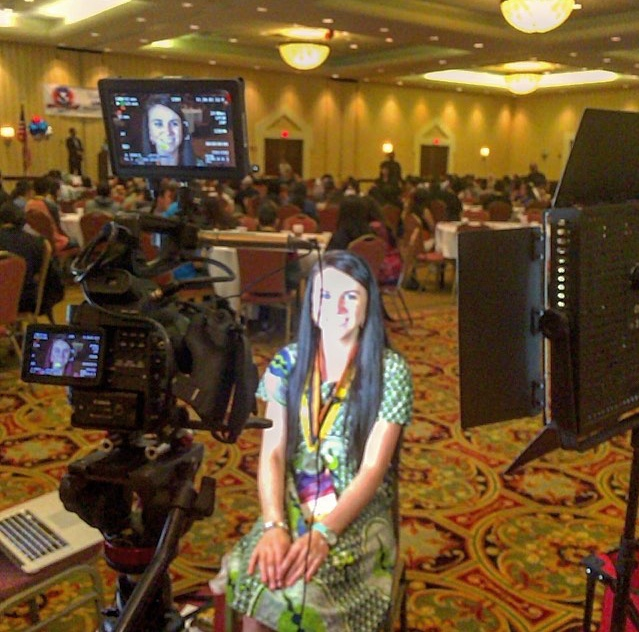 Photo of Kayla being interviewed at a UNITY event for native youth where they discussed environmental issues.