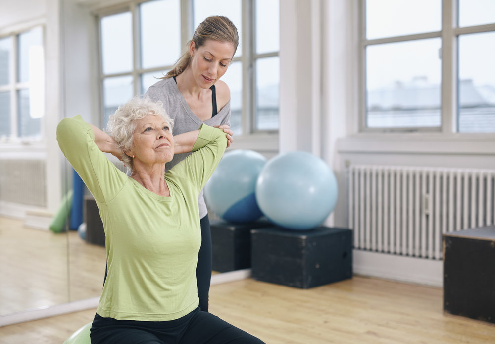mature woman and trainer doing spine extension.jpg