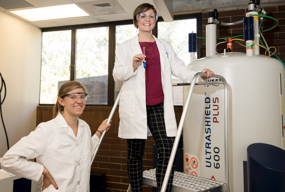 Alison and Melissa (with sample in hand) in front of the 600 MHz NMR spectrometer in the Department of Chemistry and Biochemistry.  Photo credit: Patrick Sweeney