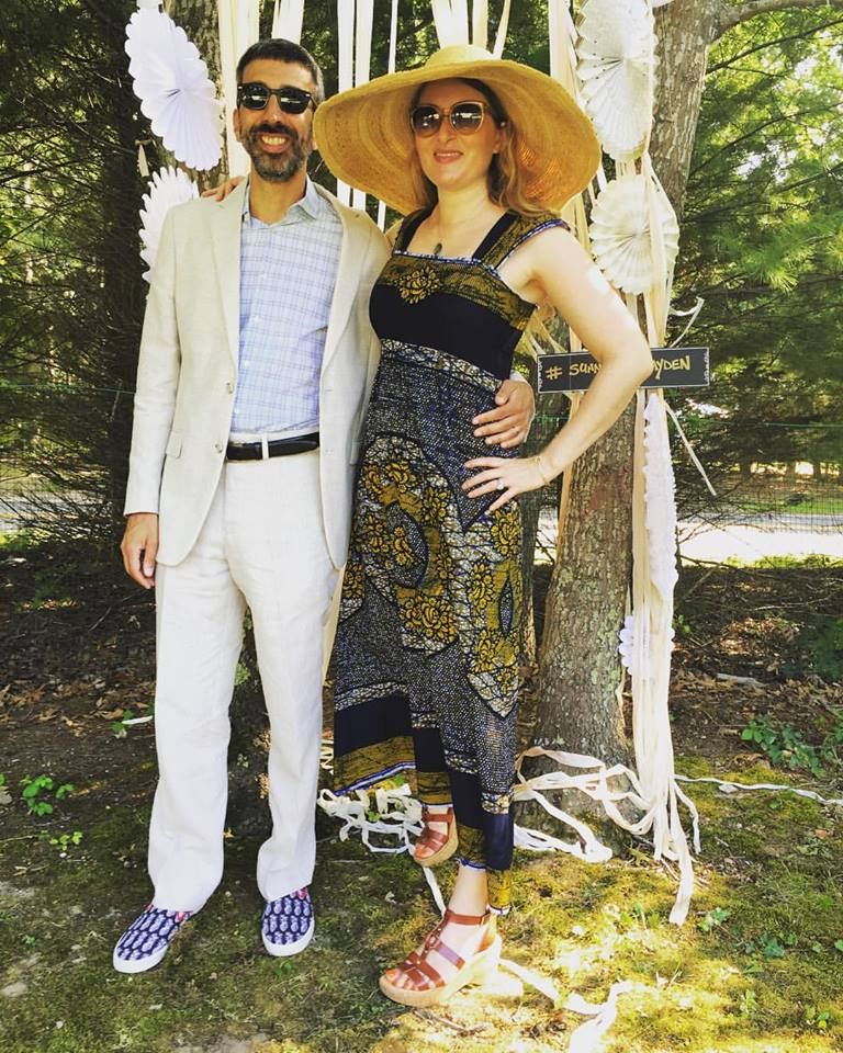 Bethany is wearing a Wax-print ankle-length dress to a summer wedding in the Hamptons - looking fabulous with her dapper husband. . .accessorized with wide-brimmed straw hat and summer sandals.