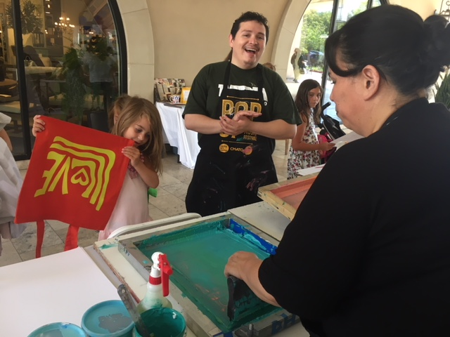 Pop-Up Art at the Oaks Mall celebrating Corita Kent's 100th Birthday with free screen printing activities led by CSUCI Professor Jasmine Delgado and assisted by her student Abel Ayala. Collaboration with City of Thousand Oaks, CSUCI, Corita Art Center and CMATO.