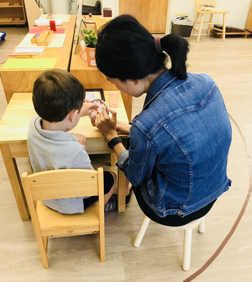 A teacher is working with a child on sewing.