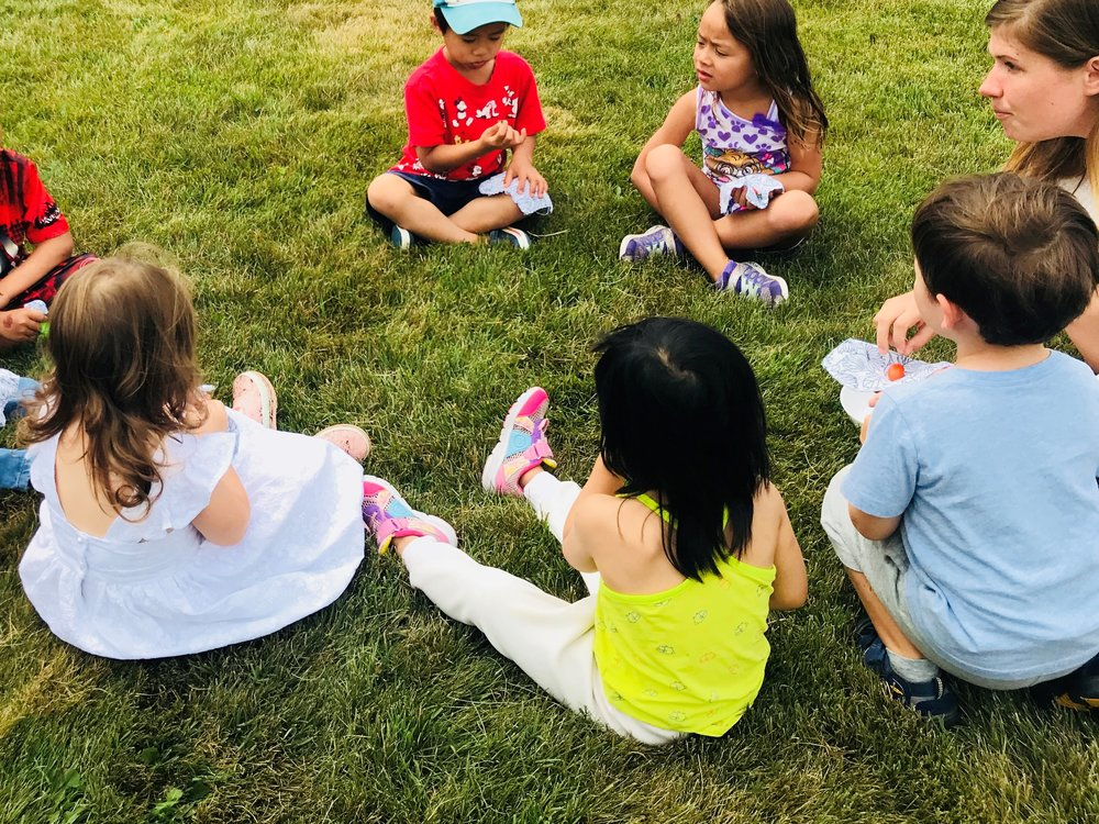 A group of children is sitting outdoors.