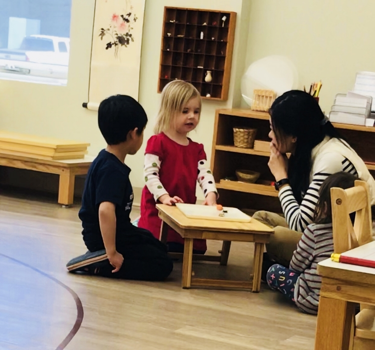 Teacher Listening To Child Describing Object