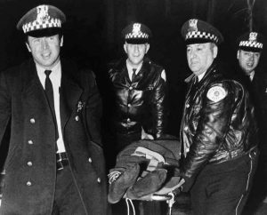 Police smile as they remove Fred Hampton's body following his assassination.